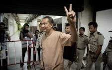 File: Activist Somyot Prueksakasemsuk reacts as he arrives at the criminal court in Bangkok on 23 January 2013. Picture: AFP.