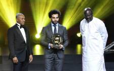 Confederation of African Football (CAF) President Ahmad Ahmad (L) poses after he hands over the 2018 African Footballer of the Year Award to Liverpool's Egyptian forward Mohamed Salah (C) alongside Liberian President George Weah during an award ceremony in Dakar, Senegal on 8 January 2019.