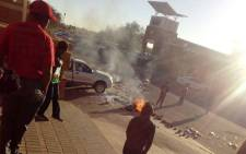 Residents walk pass stones and burning tyres outside North West Health Department head office in Mahikeng following a demonstration by staff after suspended HOD Thabo Lekalakala reported for duty. Picture: Supplied.