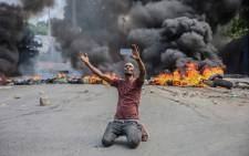 A man films himself in front of tyres on fire during a general strike launched by several professional associations and companies to denounce insecurity in Port-au-Prince on 18 October 2021. A nationwide general strike emptied the streets of Haiti's capital  on Monday, with organisers denouncing the rapidly disintegrating security situation highlighted by the kidnapping of American and Canadian missionaries at the weekend. Picture: Richard PIERRIN/AFP