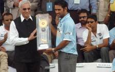 Indian one-day cricket team captain Mahendra Singh Dhoni shows off the trophy his side won in the CB ODI Tri-series in Australia in March 2008. Picture: PIB