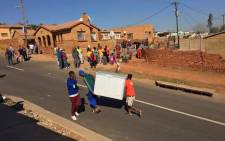 A foreign shop was looted earlier and residents decided to take the refrigerator. Picture: Kgothatso Mogale/EWN.