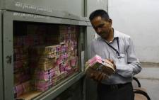 An Indian bank employee looks at deposited old demonination 1000 rupee currency notes in a bank vault in Ahmedabad on 11 November, 2016. Long queues formed outside banks in India as people crowded in to deposit old currency and withdraw new notes after the two largest denomination rupee notes were taken out of circulation. Picture: AFP.