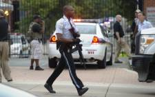 """Police respond to the report of a shooting at the Navy Yard in Washington, DC, 16 September 2013. Three gunmen shot, killed and wounded several people in a headquarters building at the US Navy Yard in Washington. Picture: Saul Loeb/AFP"""""""