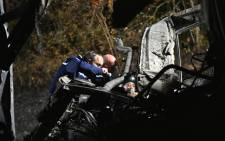 A picture taken and released on 23 October, 2015 by the French Interior Ministry shows French gendarmes inspecting the wreckage of a coach that had burst into flames after it collided with a lorry, killing at least 43 people, near the village of Puisseguin, east of Bordeaux, southwestern France. Picture: AFP.