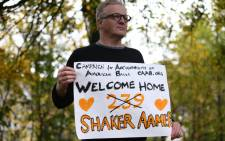 A man stands outside Biggin Hill Airport, holding a placard welcoming home Shaker Aamer, the last British resident in Guantanamo Bay, in south east London on October 30, 2015. Shaker Aamer arrived in London on Friday having earlier been freed from the US military prison in Cuba, British media reported. Picture: AFP.