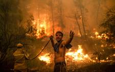 A local resident gestures as he holds n empty water hose during an attempt to extinguish forest fires approaching the village of Pefki on Evia (Euboea) island, Greece's second largest island, on 8 August 2021. (AFP)