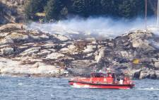 Rescue forces work at the shore west of Bergen, Norway after a helicopter transporting 13 workers from an offshore oil field in the North Sea crashed off on April 29, 2016. Rescue workers said they had seen no sign of survivors from a helicopter that crashed in western Norway with 13 people on board, but said the search was continuing. Picture: AFP.