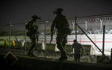 In this picture taken in the late hours on 22 August 2021 British and Canadian soldiers stand guard near a canal as Afghans wait outside the foreign military-controlled part of the airport in Kabul on 23 August 2021, hoping to flee the country following the Taliban's military takeover of Afghanistan. Picture: WAKIL KOHSAR/AFP