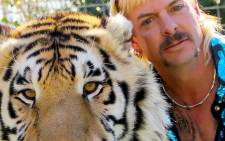 """In this file photo taken on 20 January 2020 this undated photo courtesy of Netflix shows Joseph """"Joe Exotic"""" Maldonado-Passage with one of his tigers. The US Justice Department said 20 May 2021 that it had seized 68 lions, tigers and lion-tiger hybrids as well as a jaguar from the former animal park of Joe Exotic, the star of the Netflix hit 'Tiger King'. Picture: AFP"""