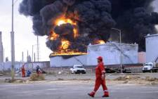 A Venezuelan PDVSA state oil company worker walks after an explosion in Venezuelan largest oil refinery Amuay on 25 August, 2012. Picture: AFP.