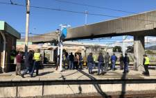 FILE: Authorities inspect a train carriage that was damaged when a fire broke out on a train at Koeberg Train Station in Cape Town. Picture: Bertram Malgas/EWN