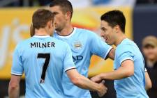 Manchester City's Samir Nasri is congratulated by James Milner and Edin Dzeko after he scored a goal against Chelsea at Yankee Stadium in New York on 25 May 2013. City beat Chelsea 5-3. Picture:  AFP
