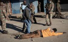 SANDF and SAPS members interrogate a suspected looter in Alexandra on 13 July 2021. This follows large-scale incidents of rioting and looting across the township and the province. Picture: Boikhutso Ntsoko/Eyewitness News