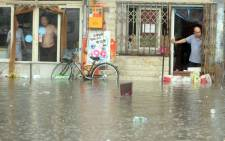 Chinese residents look at a flooded area caused by heavy rain in Beijing. At least 87 people were killed and 78 missing as torrential rain pounded northern China, state media reported on 20 July. Picture: AFP.