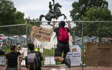 Protesters pull down a fence surrounding the statue of Andrew Jackson in an attempt to pull the statue down in Lafayette Square near the White House on 22 June 2020 in Washington, DC. Protests continue around the country over police brutality, racial injustice, and the deaths of African Americans while in police custody.  Picture: AFP.