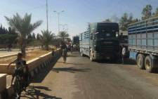 A handout picture released by the Syrian Arab News Agency (SANA) shows trucks carrying food aid arriving in Deir al-Zor on 7 September 2017. Picture: AFP