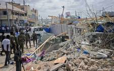 Somali security force personnel walk among debris at the site of a car bomb explosion near the building of the Interior Ministry in Mogadishu on 7 July 7 2018. Picture: AFP