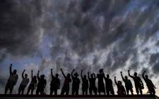 People raise their hands and shout slogans as they protest at the makeshift memorial in honour of George Floyd, on 2 June 2020 in Minneapolis, Minnesota. Picture: AFP.