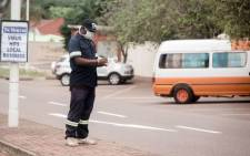 FILE: A car guard puts on surgical gloves as a preventive measure against the spread of COVID-19 in Durban, KwaZulu-Natal, on 23 March 2020. Picture: AFP.