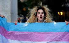 Morgin Dupont, 25, a woman of trans experience, holds up the flag for transgender and gender non-conforming people at a rally for LGBTQI+ rights at Washington Square Park on 21 October 2018 in New York City. Picture: AFP.