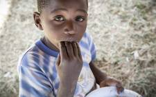 A young Mozambican boy eats some food at the camp for displaced foreign nationals in Primrose on 18 April 2015. Picture: Thomas Holder/EWN.