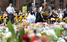 Prime Minister Tony Abbott (C-L) and his wife Margaret lay wreaths at a makeshift memorial near the scene of a fatal siege in the heart of Sydney's financial district on 16 December 2014. Picture: AFP.