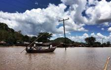 Residents of Phaloni are forced to navigate what was once a soccer pitch by boat on 22 January,2015 after the Sombani River flooded due to heavy rains. Picture: Aletta Gardner/EWN.