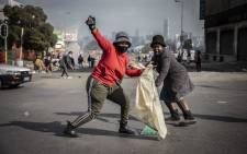 Alexandra community members cleaning up on 15 July 2021 after days of looting that saw many shops and businesses vandalised. Picture: Abigail Javier/Eyewitness News.