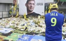 FILE: A supporter stands in front of flowers placed in front of a giant portrait of Argentinian former Nantes' forward Emilianio Sala outside La Beaujoire stadium before the French Cup football match between FC Nantes and Toulouse FC in Nantes on 5 February 2019. Picture: AFP