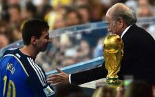 Fifa President Joseph Blatter congratulates Argentinas forward and captain Lionel Messi after he won the golden balls award after the 2014 FIFA World Cup final football match between Germany and Argentina at the Maracana Stadium in Rio de Janeiro on 13 July, 2014. Picture: AFP.