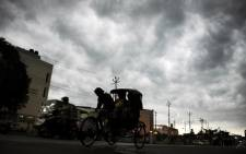 An Indian rickshaw puller transports passengers as storm clouds cover the sky. Picture: AFP.