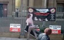 A family member of Baby Daniel's murderer takes down banners from activist group Women & Men Against Child Abuse outside the High Court in Johannesburg on 3 April 2019 following sentencing procedures. Picture: Thando Kubheka/EWN