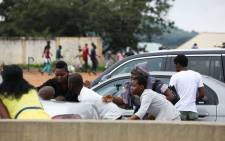 Families try to hide behind cars during clashes between police and protestors during a demonstration and attacks against South African-owned shops in Abuja, Nigeria on 4 September 2019. Picture: AFP