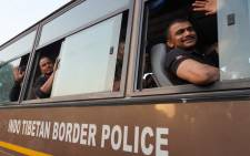 Indian nationals wave from a bus after landing at Hindon Air force station following their evacuation from Afghanistan, in Ghaziabad on 17 August 2021. Picture: Mayank MAKHIJA / AFP