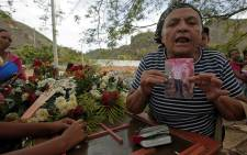 A woman holds a picture of a relative during the funeral of some of the victims of the prison fire, in Valencia, northern Carabobo state, Venezuela, 30 March 2018. Picture: AFP.
