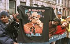Fans displays a T-shirt tribute to rapper Biggie Smalls, aka The Notorious B.I.G, on 18 March 1997 as people lined the funeral procession route through his old neighbourhood in Brooklyn. Picture: JON LEVY/AFP