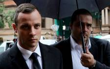 Oscar Pistorius is escorted into the North Gauteng High Court ahead of day five of his murder trial on 7 March 2014. Picture: Sebabatso Mosamo/EWN.