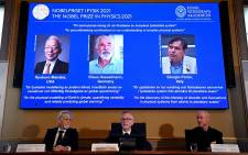 Goran K. Hansson (C), Secretary General of the Royal Swedish Academy of Sciences, and members of the Nobel Committee for Physics Thors Hans Hansson (L) and John Wettlaufer (R) sit in front of a screen displaying the co-winners of the 2021 Nobel Prize in Physics (L-R) Syukuro Manabe (US-Japan), Klaus Hasselmann (Germany) and Giorgio Parisi (Italy) at the Royal Swedish Academy of Sciences in Stockholm, Sweden, on 5 October 2021. Picture: Jonathan Nackstrand/AFP