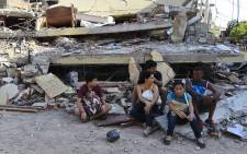 People rest in front of a destroyed house in Manta, Ecuador, on 17 April, 2016 a day after a powerful 7.8-magnitude quake hit the country. Picture: AFP.