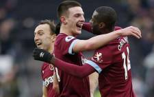 West Ham United's Irish defender Declan Rice (C) and West Ham United's Spanish midfielder Pedro Obiang (R) embrace as West Ham players celebrate on the pitch after the English Premier League football match between West Ham United and Arsenal at The London Stadium, in east London on 12 January 2019. West Ham won the game 1-0. Picture: AFP