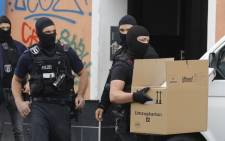 Police officers securing evidences carry boxes out of the Al-Irschad Mosque during a raid on 30 April 2020 in Berlin, as dozens of police and special forces stormed mosques and associations linked to Hezbollah in Bremen, Berlin, Dortmund and Muenster in the early hours of the morning. Picture: AFP.