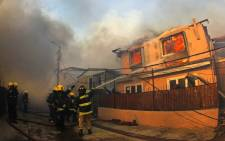 Firefighters work to extinguish the flames from a house in Valparaiso, Chile, on 2 January, 2017 as the fire threatens to reach the city's port, authorities have declared a red alert in the area. Picture: AFP.