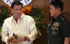 This file photo taken on 18 July 2017 shows Philippine President Rodrigo Duterte (L) holding a .45 caliber handgun, one of 3,000 units handed over during a ceremonial turn-over to the military, at Malacanang Palace as military chief Eduardo Ano (R) looks on. Picture: AFP