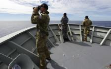 FILE: Australian Defence shows Gunner Richard Brown (L) of Transit Security Element on the lookout on the forecastle of HMAS Perth in the search for missing Malaysia Airlines flight MH370 in the southern Indian Ocean on 9 April 2014. Picture: AFP.