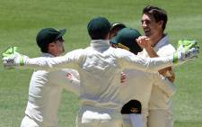 Australia fast bowler Pat Cummins (R) and teammates celebrate the dismissal of India's Jasprit Bumrah during day five of the second Test between Australia and India in Perth on 18 December 2018. Picture: AFP