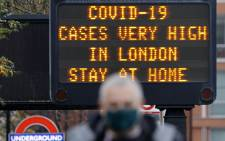 "FILE: In this file photo taken on 23 December 2020, a pedestrian walks past a sign alerting people that ""COVID-19 cases are very high in London - Stay at Home"", in central London. Picture: AFP"