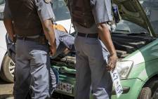 Police inspect a suspected vehicle of licensing fraud at the Rand West City Local Municipality. The owner had numerous registration papers and license plates in the vehicle, and the license disk did not match the registration plates. Picture: Thomas Holder/EWN.
