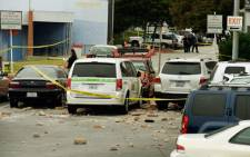 Law enforcement personal invstigate the shooting scene where an SUV crashed throught the wall of a parking lot and hit several cars across the street from the Santa Monica College weher a multiple shootings happened on campus 7 June 2013 in Santa Monica, California. Picture: AFP