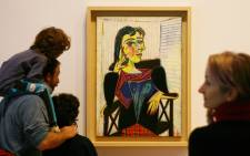 FILE: Picasso's portrait of Dora Maar, looks at visitors to the exhibition titled 'Picasso: Love & War 1935-1945' which explores the personal and artistic relationship between Pablo Picasso and his lover and muse of those years, Dora Maar, at the National Gallery of Victoria, in Melbourne 3 July 2006. Picture: AFP